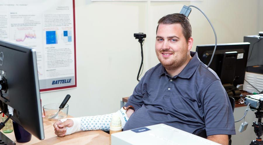 Ian Burkhart is seated in front of a computer monitor. His is wearing the sleeve on his right arm. A cable connects the implanted microelectrode array to the computer equipment.