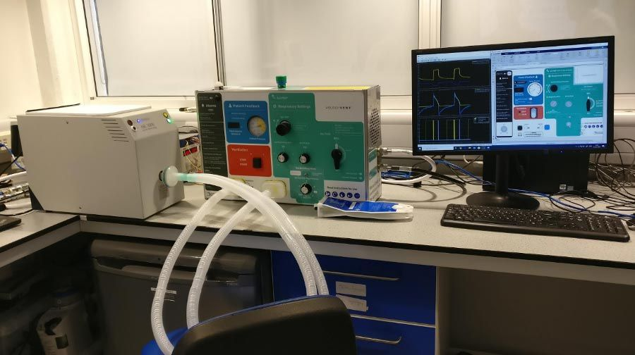 On a desk in an office, the testing configuration comprises an ASL-5000 artificial lung (left) with two breathing tubes that connect to the ventilator (middle). The PC on the right-hand side is running the Simulink model for a hardware-in-the-loop test.