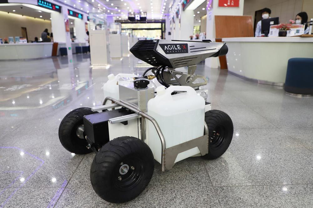 A disinfecting robot carrying two tanks of liquid disinfectant inside a commercial space. It has four wheels and a spray attachment.