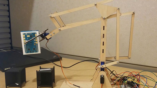 See how a robotic arm is lifting an object and placing it on top of another while being controlled from a remote location.